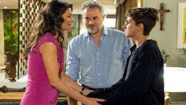 Joyce segura nas mãos do filho e Eugênio a observa