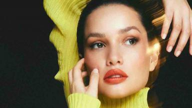 Juliette de blusa de lã amarela com mãos no rosto