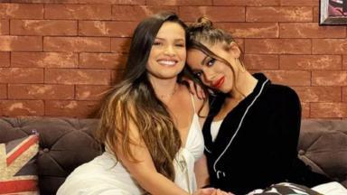 Juliette e Anitta sentadas em um sofá e abraçadas