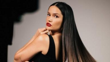 Juliette de perfil, roupa preta, cabelo liso e batom vermelho