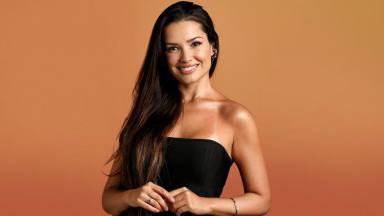 Juliette sorrindo com fundo laranja e um tomara que caia preto
