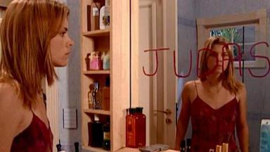 Camila olhando a palavra Judas no espelho do banheiro