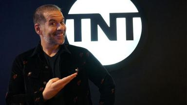 Leandro Hassum aponta para o logo do TNT sorrindo