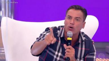 Leo Dias com microfone na mão e apontando o dedo