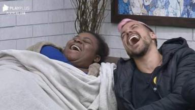 Sentados no sofá da sala, Jojo e Lipe dão risada em A Fazenda 2020