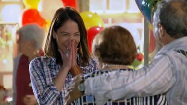 Lorena com a mão no rosto de alegria