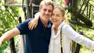 Luciano Huck e Angélica no meio da mata sorrindo