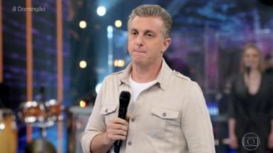 Luciano Huck com microfone na mão e fazendo expressão com a boca
