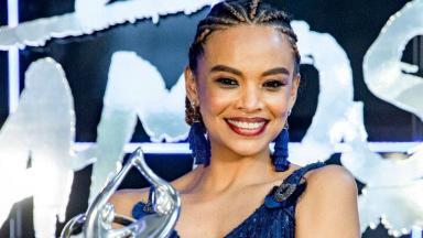 Lucy Ramos posada sorridente com o troféu da Dança dos Famosos