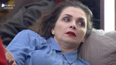 Luiza Ambiel de camisa azul e batom vermelho olhando para o lado
