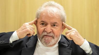 Lula sentado com a mão na cabeça