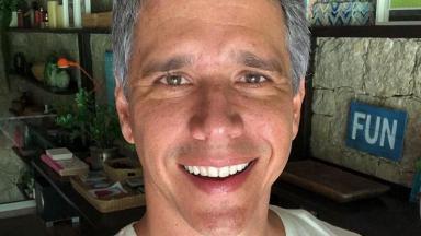 Márcio Garcia sorridente na sala da sua casa