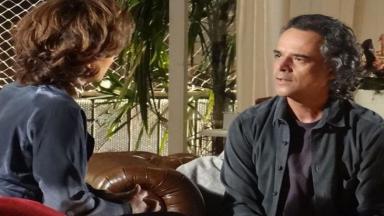 Vitória e Marcos sentados de frente um para o outro enquanto conversam