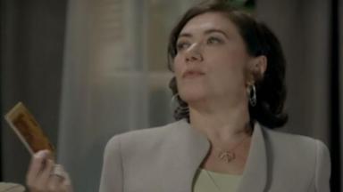 Maria Marta olha para Cristina com ar de superioridade e um talão de cheques na mão