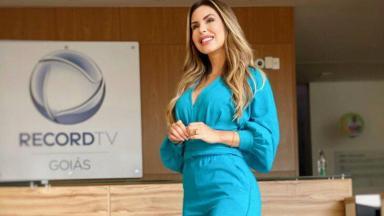 Mariana Martins posada próximo ao logo da Record