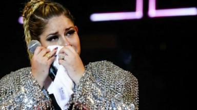 Marília Mendonça segurando microfone e limpando o rosto após chorar