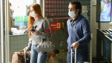 Marina Ruy Barbosa e Guilherme Mussi desembarcando em São Paulo com malas na mão