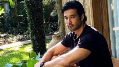 Sergio Marone sentada em meio a um cenário natural