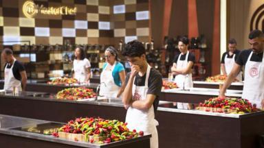 Participantes olhando para bancada cheia de pimentas