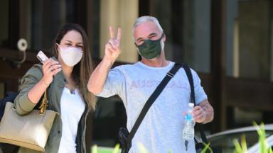Mateus Carrieri de máscara, fazendo sinal para paparazzo, ao lado da namorada