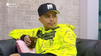 Matheus Yurley de boné, casaco, segurando uma caneca sentado no sofá do Power Couple Brasil