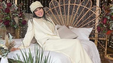 Mayra Cardi de boina na cabeça, sorridente, sentada em uma cama de casal
