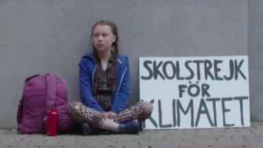 Greta Thunberg sentada em protesto