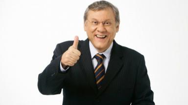 Milton Neves fazendo sinal positivo com a mão direita e sorrindo