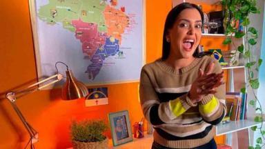 Mona Lisa Duperron esfregando as mãos com mapa ao fundo