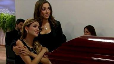 Nikki e Lili abraçadas em frente ao caixão de Nelson