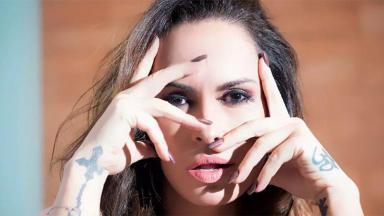 Nubia Oliiver com pose séria com as mãos no rosto