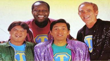 Foto dos Trapalhões Zacarias, Mussum, Dedé e Didi sorridentes usando jaquetas coloridas e camiseta com a letra T