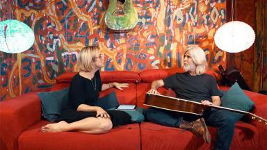Paloma Duarte e Owaldo Montenegro sentados no sofá conversando
