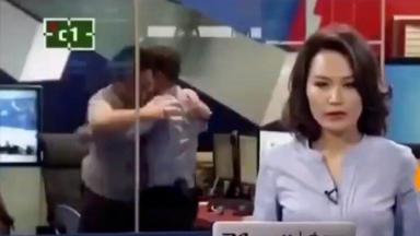 Dois homens se atracando na redação do jornal, enquanto a apresentadora dá as notícias