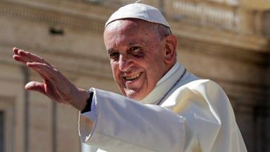 Papa Francisco sorrindo com a mão levantada