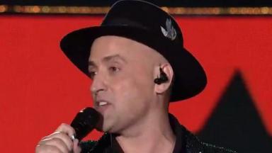 Paulo Gustavo de chapéu e segurando microfone