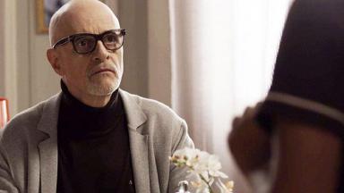 O ator Marcos Caruso de óculos de grau e com as mãos cruzadas em cena da novela Pega Pega