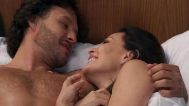 Henrique e Penélope abraçados, na cama, ele olha para ela que sorri
