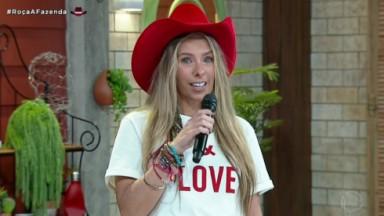 Adriane Galisteu de chapéu vermelho e blusa escrito love