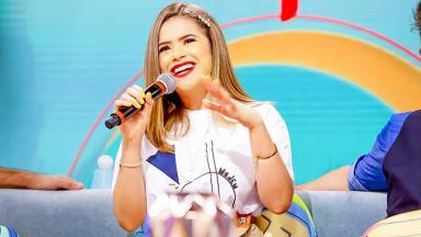 Maisa sorrindo com o microfone na mão