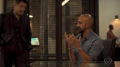 Raul de pé, com as mãos no bolso, olha para Álvaro sentado com as mãos levantadas o