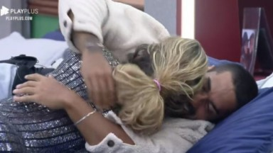 Deitado na cama, Bil Araújo abraça Erika Schneider e dá um beijo no pescoço da peoa