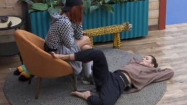 Dayane Mello está deitada no chão enquanto conversa com Valentina Francavilla na sala de A Fazenda 2021