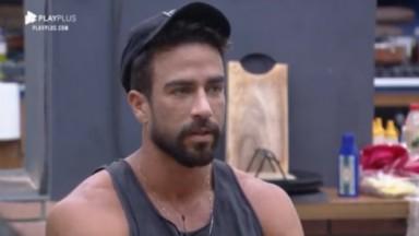 Erasmo Viana sentado na cozinha falando mal de colegas de confinamento em A Fazenda 2021