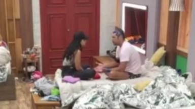 Victor Pecoraro e Aline Mineiro estão sentados na cama conversando