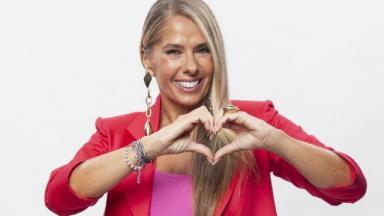 Adriane Galisteu fazendo sinal de coração