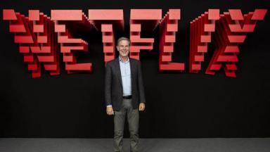 Reed Hastings com Netflix ao fundo