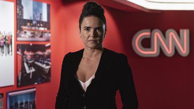 A CEO Renata Afonso posando para foto, séria, tendo ao fundo o logo da CNN Brasil