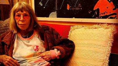 Rita Lee posada no sofá de casa