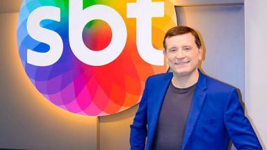 Roberto Cabrini com o logo do SBT ao fundo